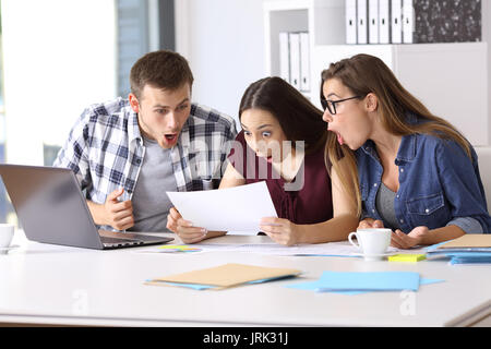 Three amazed employees reading a paper document at office - Stock Photo