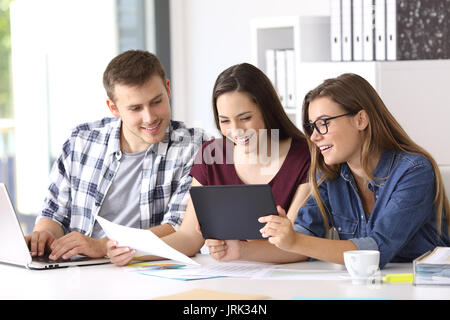 Three happy employees working on line with a tablet and documents at office - Stock Photo
