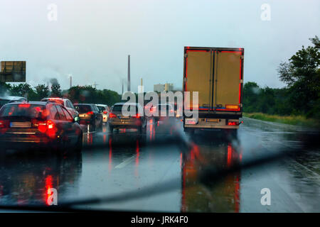 Danger of a traffic jam in heavy rain. Severe weather on the highway and bad driving conditions. - Stock Photo
