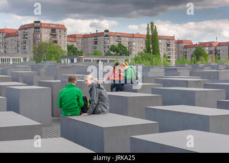 Berlin Holocaust Memorial, a group of young students chat to each other during a visit to the Holocaust Memorial - Stock Photo