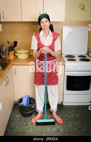 A depressed  adult woman, a housewife or a maid, wearing a red apron and a green scarf on her head is resting after - Stock Photo
