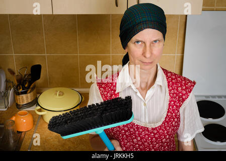 An angry and tired adult woman portrait, a housewife, a maid or maybe a witch, wearing a red apron and a green scarf - Stock Photo