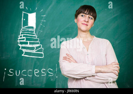 Woman smiles writes on a blackboard the concept of success - Stock Photo