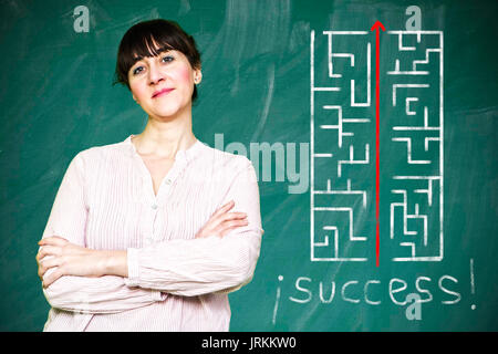 Woman smiles writes on a blackboard to learn concept - Stock Photo