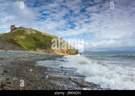 The beach at Castle at Criccieth, North Wales, during a high tide on a bright summer day - Stock Photo