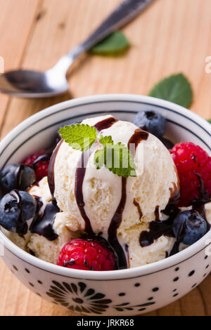 vanilla ice cream with fruits in a white bowl - Stock Photo