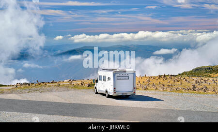 Motor home paring on a mountain plateau above the clouds - Stock Photo