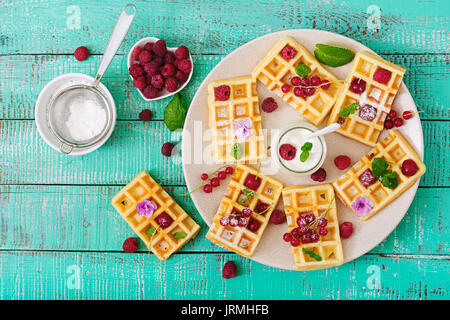 Belgium waffles with raspberries and yogurt on plate. Flat lay. Top view - Stock Photo