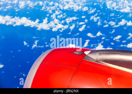 Wing of an airplane flying above the clouds on a clear sunny day. Aircraft flying high through the cumulus clouds. - Stock Photo