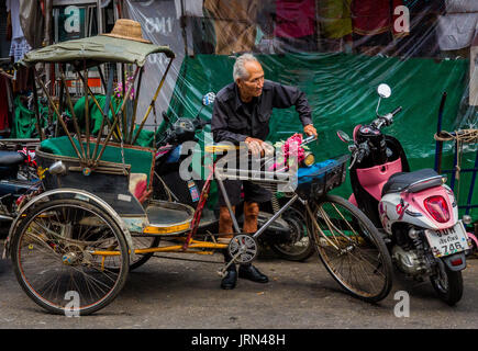 Cycle rickshaw driver with bike in the Old City in Chiang Mai, Thailand. - Stock Photo