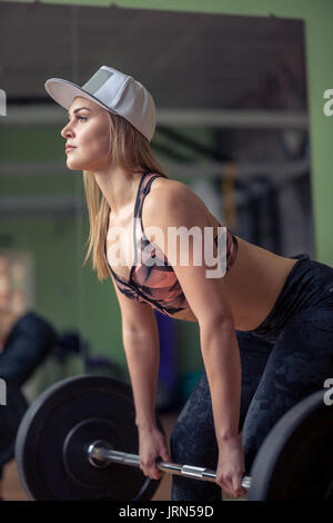 Athletic female fitness model holding heavy barbell and preparing for deadlift. - Stock Photo