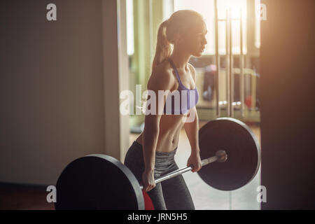 female powerlifter preparing for deadlift of barbell during competition of powerlifting - Stock Photo