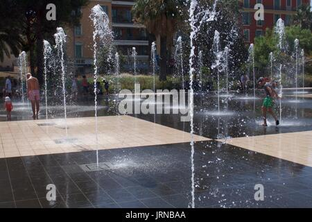 Father and toddler splashing in water fountains at Massena Square, Nice, France - Stock Photo