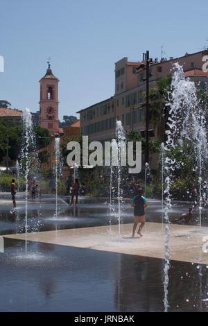 Children splashing in water fountains at Massena Square, Nice, France - Stock Photo