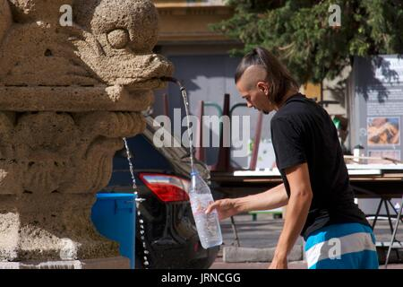 Male tourist filling plastic bottle at water fountain, Nice, France - Stock Photo
