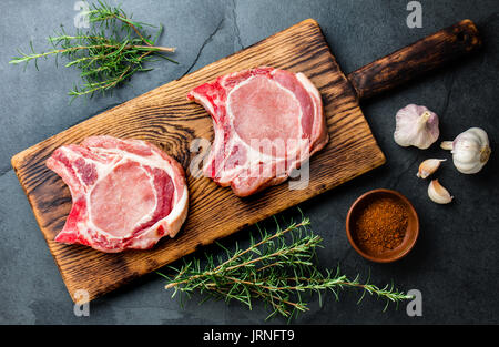 Raw pork cutlet chop for fry on pan with herbs, garlic on wooden boards, slate gray background. - Stock Photo