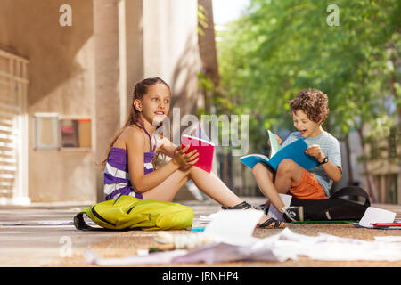 Happy boy and girl with textbooks near the school reading talking smiling - Stock Photo