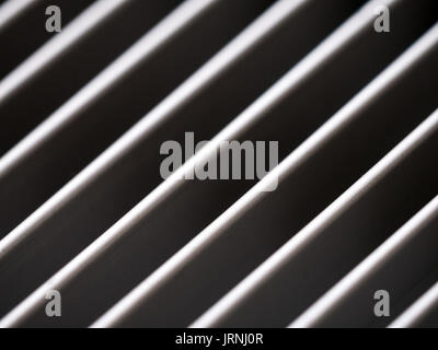 Close-up of aluminum cover grille with pattern of diagonal lines in shadow and light, black and white - Stock Photo