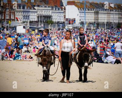 Weymouth, Dorset, UK. 6th Aug 2017. Holiday makers enjoying a Sunday on the beach on a breezy sunny day on the south - Stock Photo