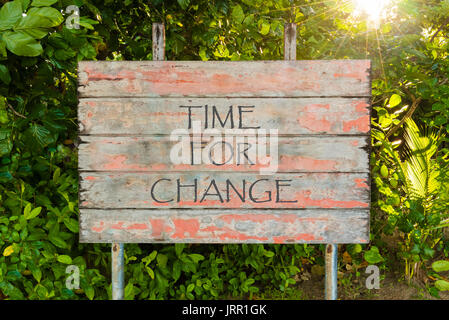 Time For Change motivational quote written on old vintage board sign in the forrest, with sun rays in background. - Stock Photo