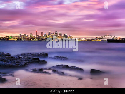 Distant panorama of Sydney CBD cityline from sandy beach with rocks at Harbour's Bradley's head at sunset. Brightly illuminated australian landmarks u