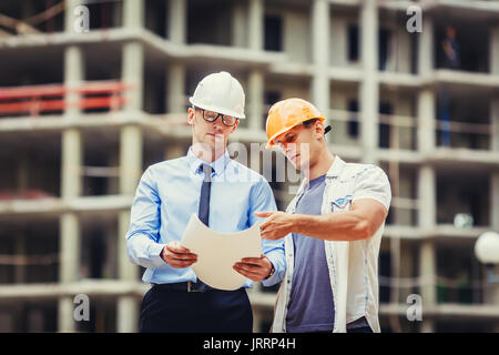 Architect and builder discussing at construction site - Stock Photo