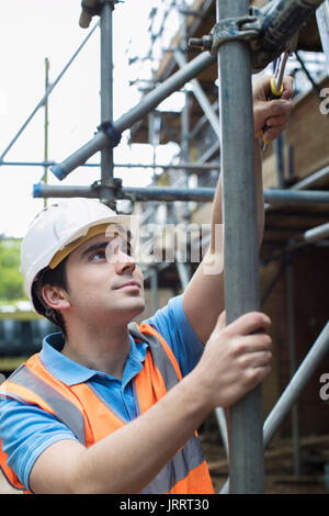 Builder On Site Putting Up Scaffolding - Stock Photo