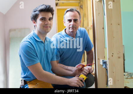 Portrait Of Electrician With Apprentice Working In New Home - Stock Photo