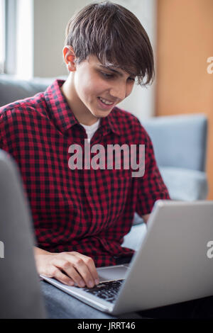 Teenage Boy Working On Laptop At Home - Stock Photo