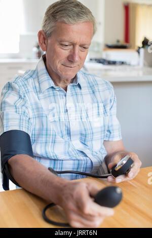 Mature Man Measuring Blood Pressure At Home - Stock Photo
