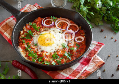 Shakshuka in a Cast Iron Pan. Middle eastern style eggs poached in tomato and pepper sauce with parsley, onion and - Stock Photo