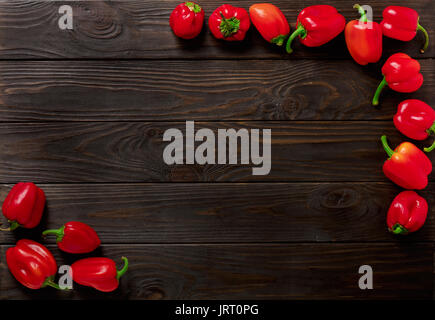 Sweet bulgarian red peppers on a dark wooden background. Selective focus. - Stock Photo