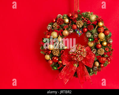 A Christmas wreath. decorated with balls, ribbons, pine cones, sea shells and bells hangs against a red background. - Stock Photo