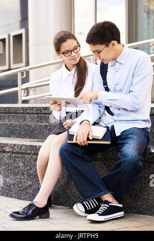 Schoolchildren Using Digital Tablet Outdoors - Stock Photo
