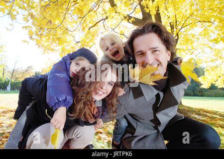 Parents giving children piggyback ride in yellow autumn park - Stock Photo