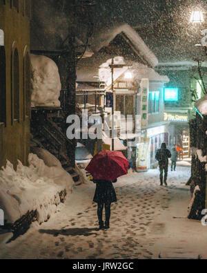 Woman walking down the street in Nozawa Onsen on a snowy night holding a pink umbrella. - Stock Photo
