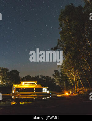Houseboat parked on the mighty Murray River at night under the stars with a camp fire on the banks near Echuca. - Stock Photo