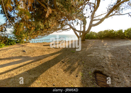 Lonely bench at golden hour at the Scripps Panoramic landscape picture of a lonely wooden bench with scenic ocean - Stock Photo