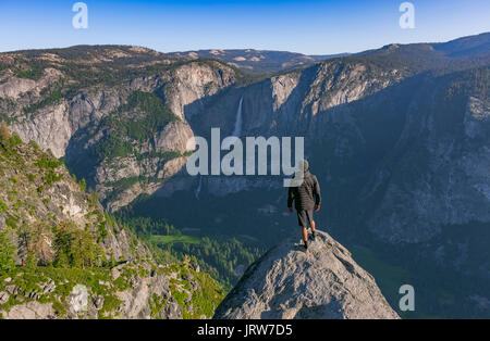 Panoramic views from Glacier Point of Yosemite Falls. Standing on a cliff and looking down at the valley at sunrise - Stock Photo