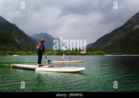 Mother and son in a wet suit paddling on SUP on alpine lake, Lago di Predil, Itlay.