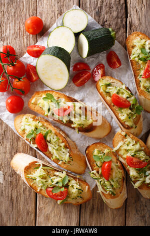 Italian bruschetta with zucchini and tomatoes close-up and ingredients on the table. Vertical view from above - Stock Photo