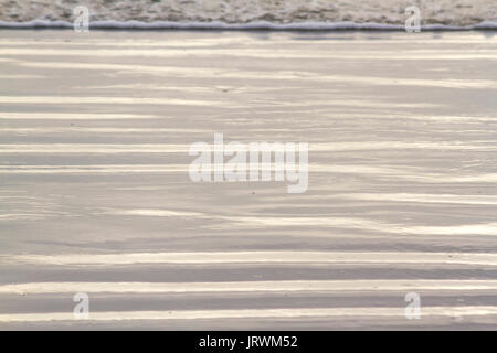 Close up photography of natural abstract patterns on the beach created by wet sand and small waves in the late afternoon - Stock Photo