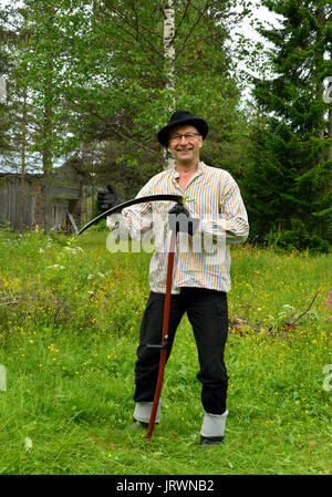 Middle-aged Farmer in old vintage clothes mows grass on lawn traditional wooden scythe - Stock Photo