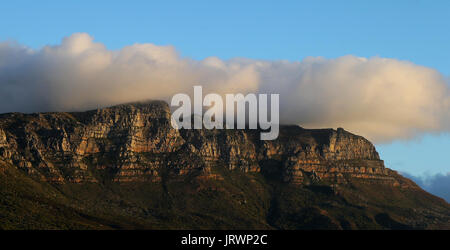 Clouds form on top of Table Mountain and the Twelve Apostles as seen at sunset from Camps Bay beach in Cape Town, - Stock Photo