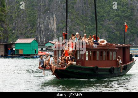 Tourists in Chinese Junk, Halong Bay Tourist Boat Tour, Vietnam. Junk, boat sailing amongst karst limestone mountains - Stock Photo