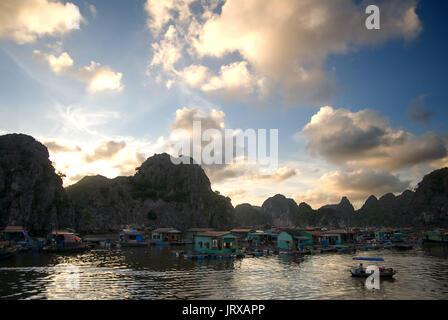 Floating fishing village in Halong Bay. Fish farm village amongst karst limestone mountains at Cat Ba National Park, - Stock Photo