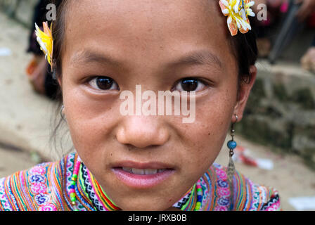 Bac Ha market. Flower Hmong girl in traditional dress at weekly market, Sapa, Vietnam. Young women from the Flower - Stock Photo