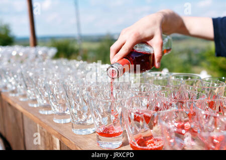 Bartender pouring cocktail in glasses - Stock Photo