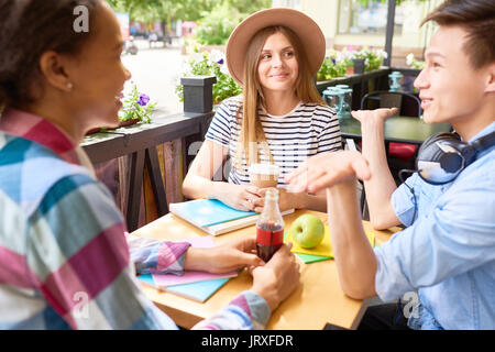 Students Enjoying Lunch in Outdoor Cafe - Stock Photo