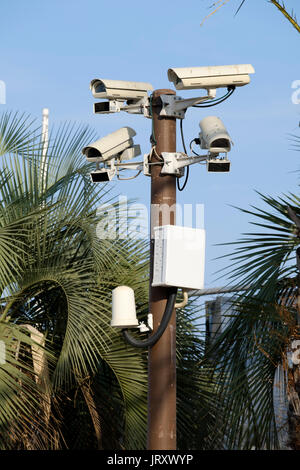 A group of CCTV cameras mounted on a pole keep surveillance and assist with security vigilance by monitoring the - Stock Photo